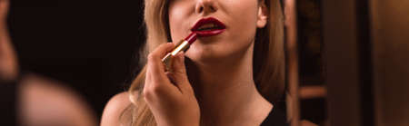 rich life: Woman is doing her make-up in front of the mirror Stock Photo