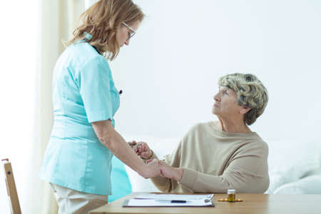 senescence: Picture of medic visiting her female old patient at home Stock Photo