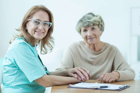 medic: Picture of kind female medic with her aged patient