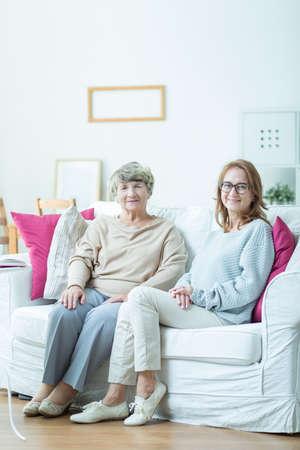 personas sentadas: Foto de la mujer mayor que se sienta en el sof� con su cuidador