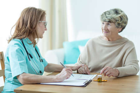 senescence: Female doctor on medical home appointment talking with elderly patient