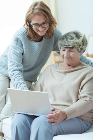 old people: Picture of smiling carer teaching old woman computer skills Stock Photo