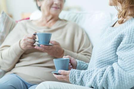 dialogo: Dos mujeres mayores que beben el caf� durante la conversaci�n en casa
