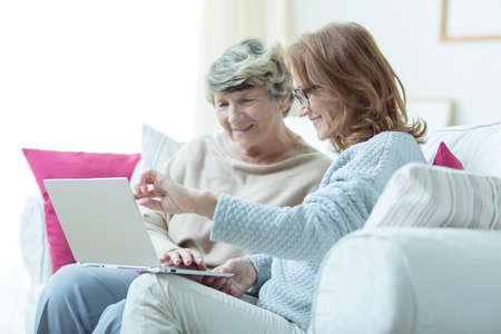 Beeld van soort verzorger onderwijs oude dame om laptop te gebruiken Stockfoto