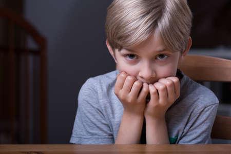 Foto van blonde bange jongen zitten aan tafel