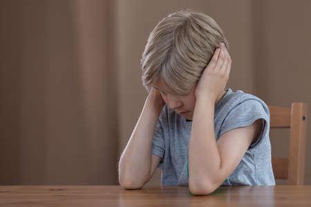 psicologia infantil: Imagen del muchacho joven que tapa los oídos con las manos deprimidas