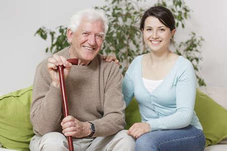 Glimlachend senior man die kan en ondersteunende kleindochter