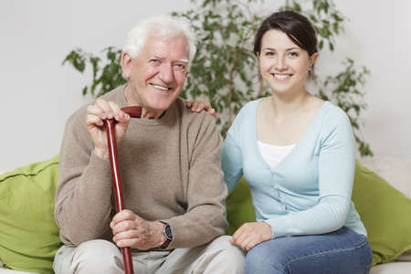 cane sofa: Smiling senior man holding can and supporting granddaughter