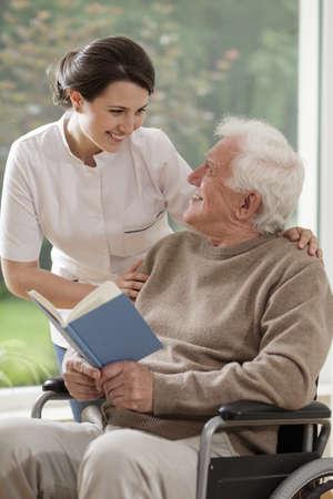 libros viejos: Enfermera que cuida habla con el paciente mayor lisiado Foto de archivo