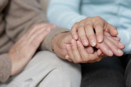 manos: Primer plano de la nieta apoyar su abuelo alto Foto de archivo