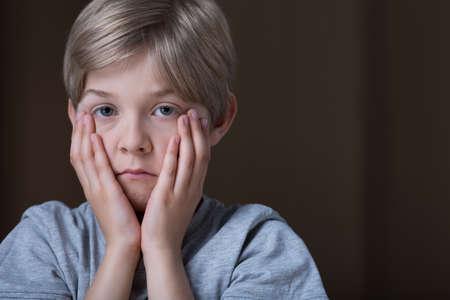 彼の手で顔を保持している悲しい落ち込んでいる子の肖像画 写真素材