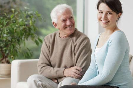 eldercare: Smiling grandpa and caring granddaughter at home