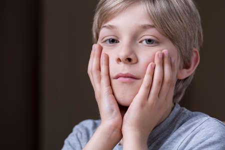 ojos tristes: Close up de niño pequeño infeliz sosteniendo la cara entre las manos