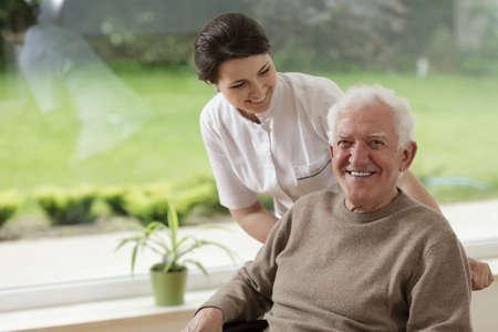 Glimlachend senior man verblijft in verpleeghuis Stockfoto