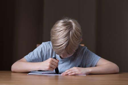 psicologia infantil: Imagen de un niño con problemas mentales de dibujo con lápices de colores negro