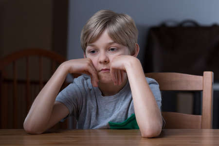 dissatisfied: Picture of dissatisfied small blonde kid sitting at table