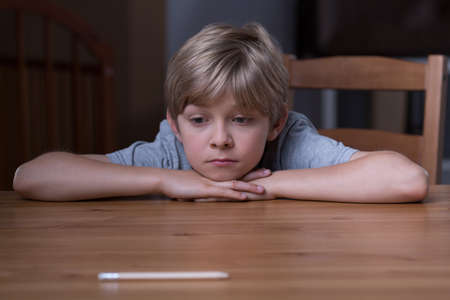 Image of small depressed boy laying his head on hands Stock Photo