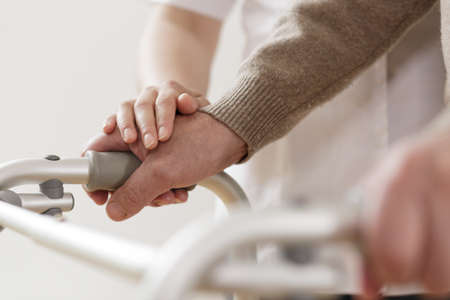 rehabilitation: Close-up of physiotherapist supporting disabled senior man