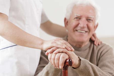 ancianos caminando: Hombre mayor sonriente y ayudar a la enfermera útil Foto de archivo