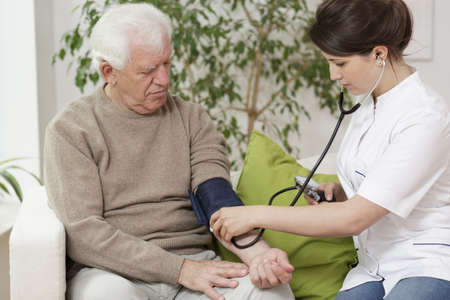 pressures: Doctor measuring blood pressure of elder man