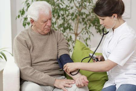 hipertension: Medición de la presión arterial del doctor anciano