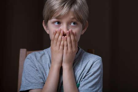 scared child: Retrato de ni�o asustado de la mano en la boca