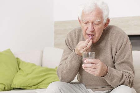 Hombre mayor enfermo tomar medicamentos para la hipertensión