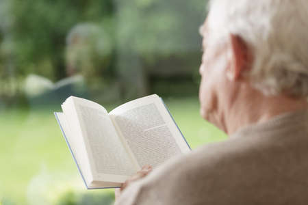 old people: Elder man sitting and reading interesting book Stock Photo