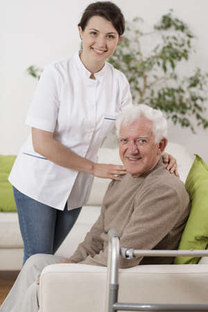 social care: Young physiotherapist supporting senior patient during rehabilitation