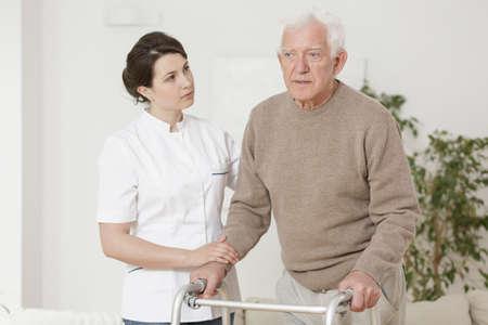 assisting: Senior man using walking frame during rehabilitation Stock Photo
