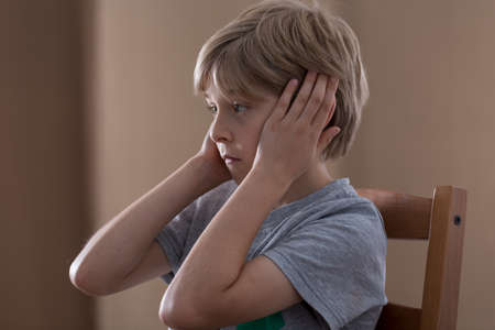plugging: Image of sad small boy plugging ears with hands