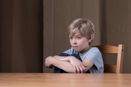 足を抱いて椅子に座っている不幸な子供の画像 写真素材