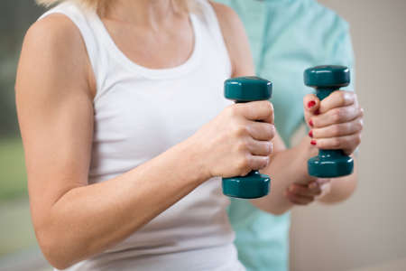 physiotherapists: Close-up of woman at physiotherapists cabinet holding dumbbells