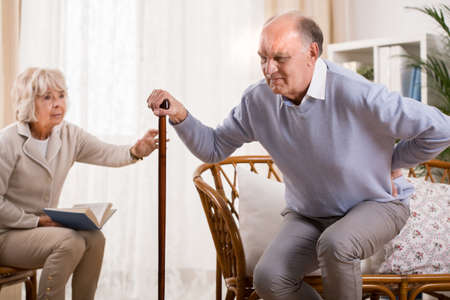 senior pain: Aged man with walking stick and terrible backache