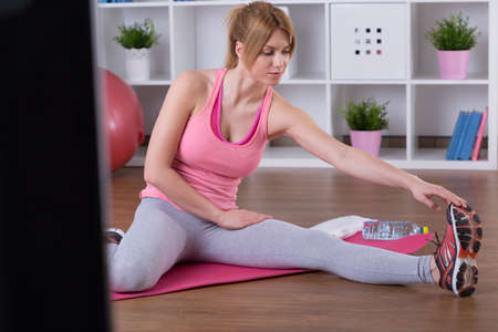 stretched: Stretched woman doing exercise on floor mat