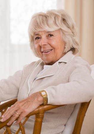 woman alone: Smiling elderly elegant woman relaxing in armchair