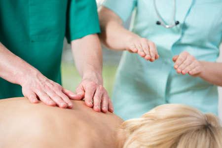 fisioterapia: Fisioterapeuta experimentado corregir el estudiante durante el masaje