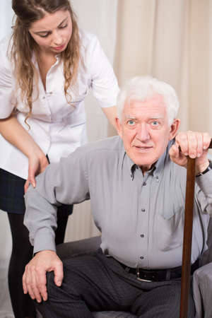 Elder man trying to get up with walking stick assurance Stock Photo