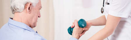 sanitarium: Elder man exercising his muscles with a dumbbell Stock Photo