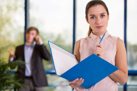 Beauty female office worker holding blue folder Stock Photo