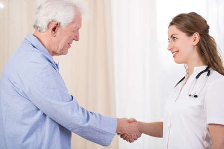 senility: Nurse having medical visit in her patients house Stock Photo