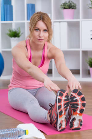 hamstring: Sporty woman stretching hamstring muscles on the floor mat