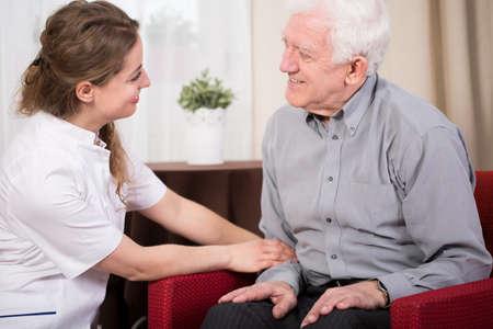 nurse: Terapeuta joven durante la visita a la casa del paciente anciano Foto de archivo