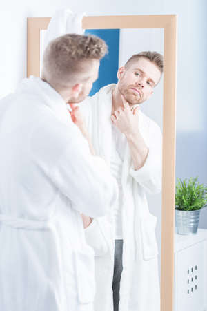 narcissistic: Pretty self-centered man admiring himself in the mirror Stock Photo