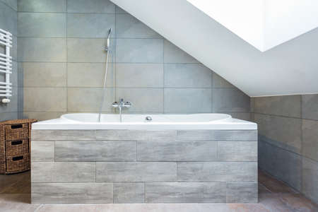 Vertical view of bathtub with wooden housing