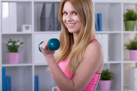 woman muscle: Smiling beauty woman doing exercise with dumbbell