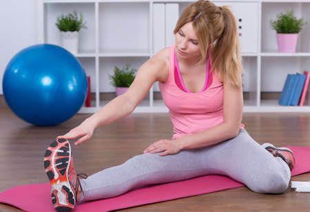 hamstring: Fit woman stretching legs after domestic training