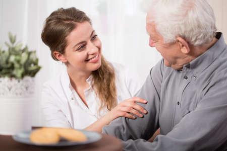 pozitivní: Mladý dobrovolník na návštěvě starší muž v nouzi