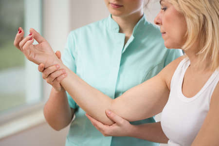 Close-up of young physiotherapist flexing the elbow Stock Photo