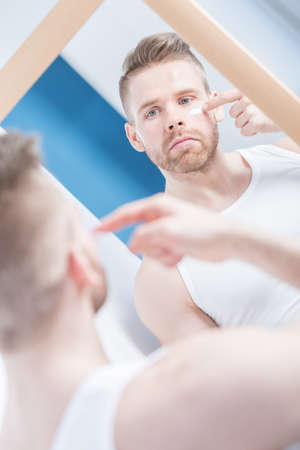 narcissistic: Handsome self-involved man looking at single wrinkle on face